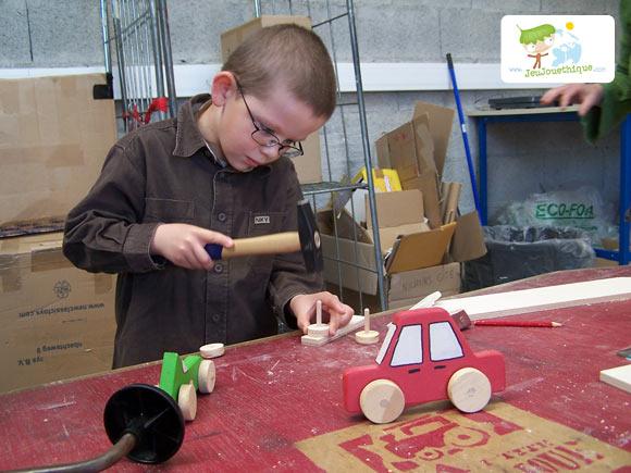 Enfant qui tape avec un marteau pour construire son jouet en bois