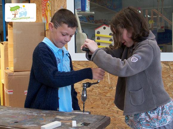 Enfant perçant son jouet en bois avec une chignolle