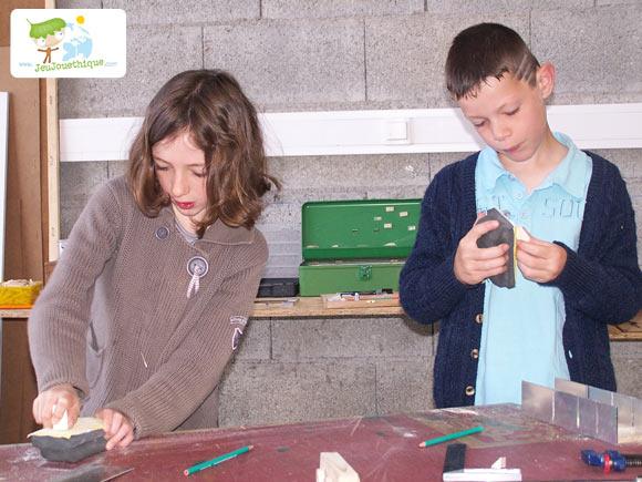 Enfant qui ponce du bois pour construire son jouet