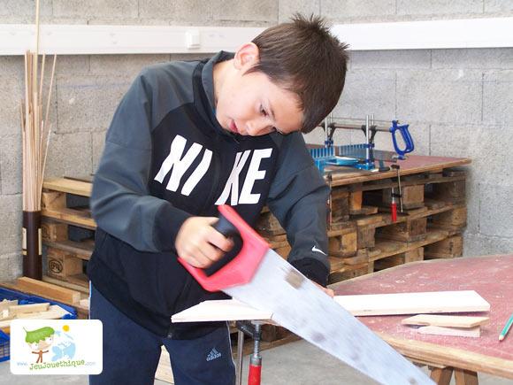 Enfant qui sciant du bois pour construire son jouet