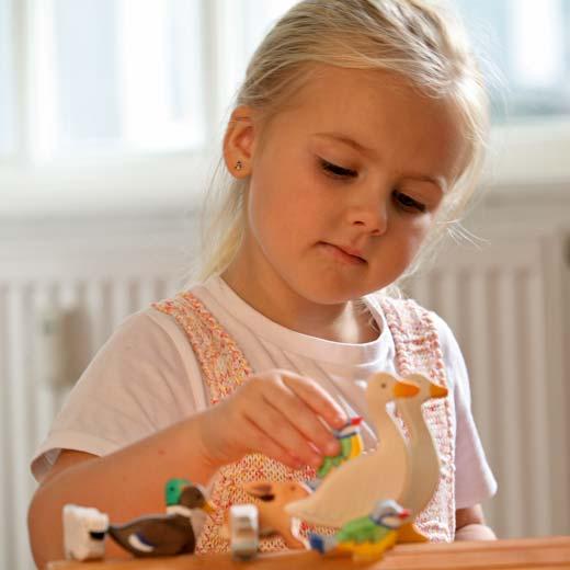 Enfant qui joue avec des figurines holztiger